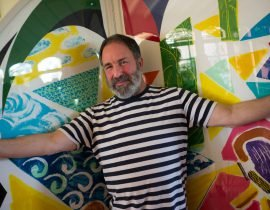 Peter Shire in front of a David Hockney screen.